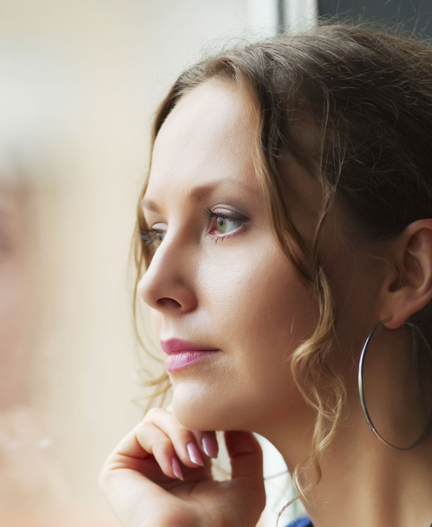 young woman thinking out window considering abortion